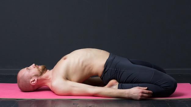 Homem com torso nu está deitado no tapete, dobrando as costas