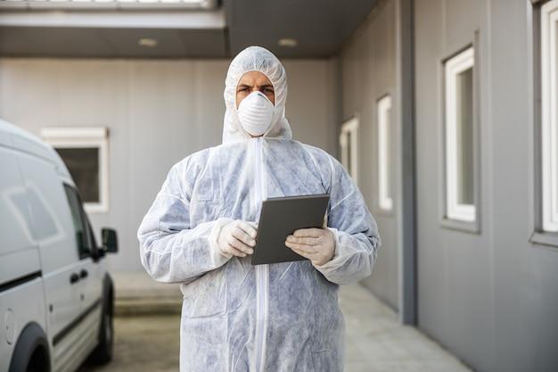 Homem com traje de proteção contra vírus e máscara olhando e digitando no tablet, desinfetando edifícios de coronavírus com o pulverizador. epidemia.