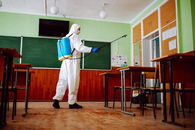 Homem com traje de proteção desinfetando uma sala de aula