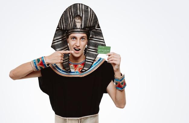 Homem com traje egípcio antigo segurando um cartão de crédito apontando com o dedo indicador para ele, sorrindo alegremente feliz e satisfeito no branco