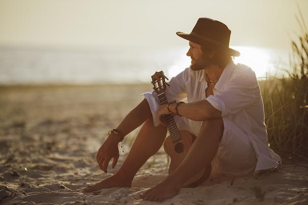 Homem com ukulele durante as férias de verão na praia perto do mar