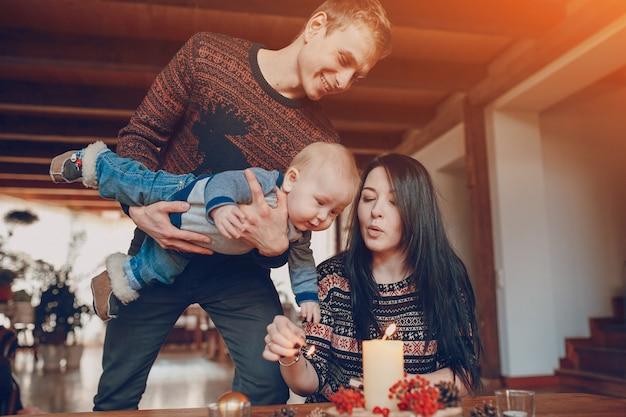 Homem com um bebê em suas mãos olhando para sua esposa acender uma vela