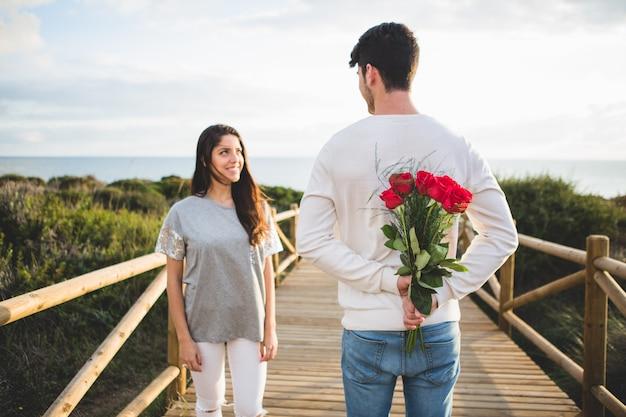 Homem com um buquê de rosas nas costas olhando para sua namorada