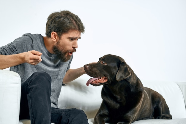 Homem com um cachorro preto em um sofá branco sobre um fundo claro close-up recortado vista animal de estimação humano amigo emoções diversão. foto de alta qualidade