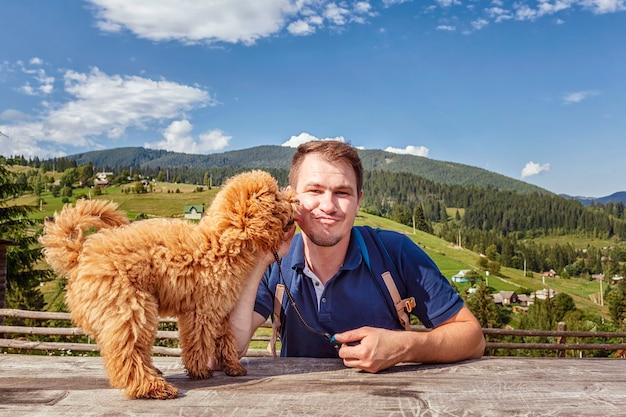 Homem com um cão poodle em um fundo de paisagem montanhosa