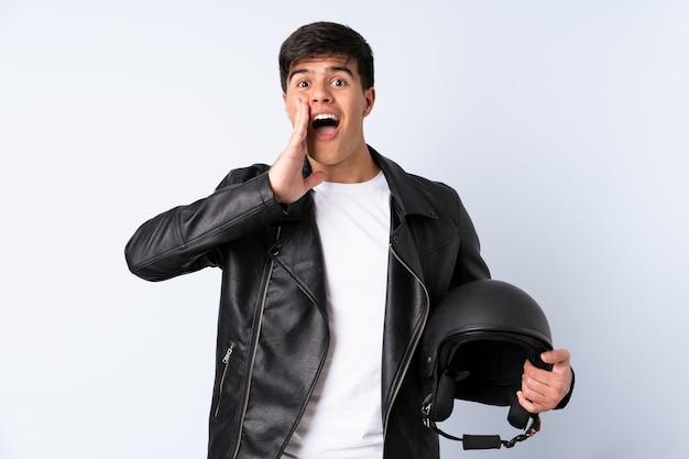 Homem com um capacete de moto ao longo da parede azul, gritando com a boca aberta