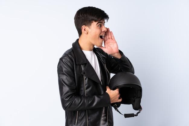 Homem com um capacete de moto sobre fundo azul isolado, gritando com a boca aberta