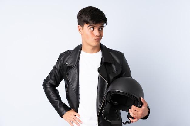 Homem com um capacete de moto sobre parede azul, pensando em uma idéia