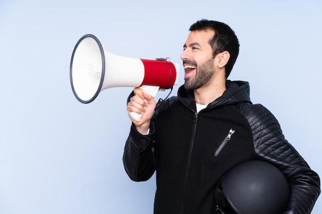 Homem com um capacete de moto sobre parede isolada gritando através de um megafone