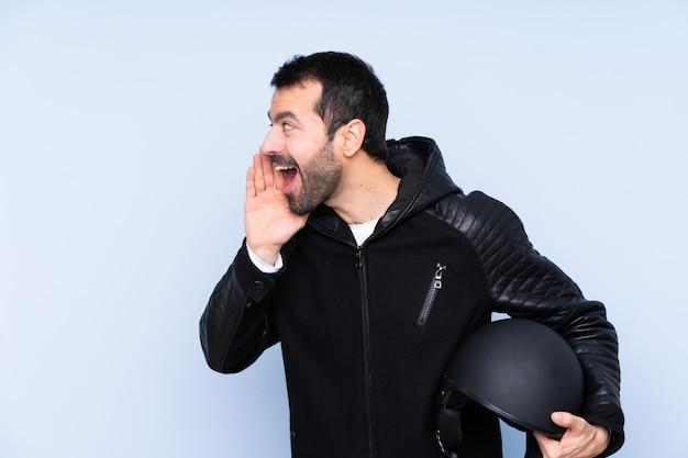 Homem com um capacete de moto sobre parede isolada, gritando com a boca aberta para a lateral