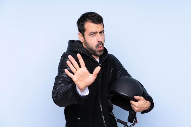 Homem com um capacete de moto sobre parede isolada nervosa, esticando as mãos para a frente
