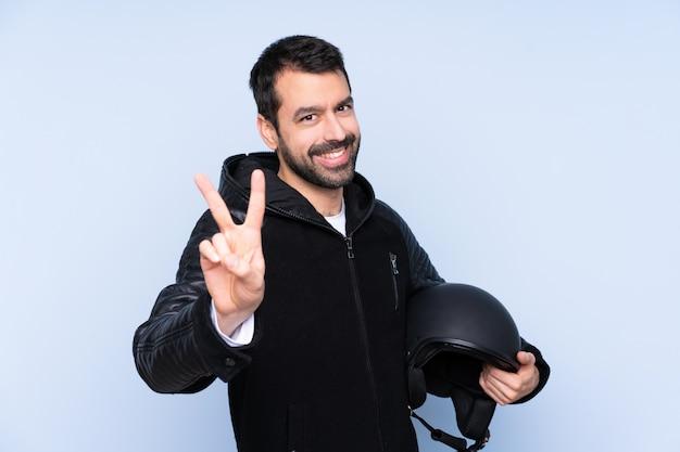 Homem com um capacete de moto sobre parede isolada sorrindo e mostrando sinal de vitória
