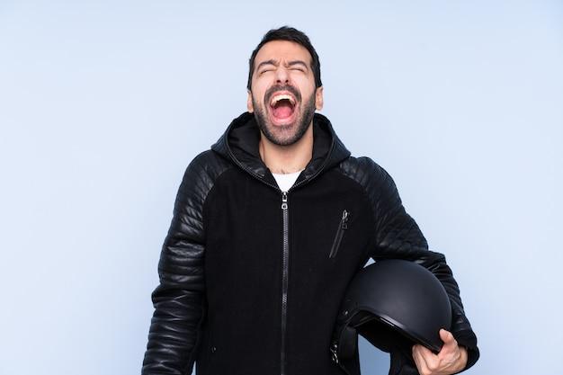 Homem com um capacete de moto sobre parede isolada