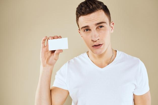 Homem com um cartão de visita nas mãos de um gerente de escritório. fundo bege