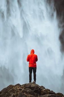 Homem com um casaco vermelho na cachoeira haifoss, islândia