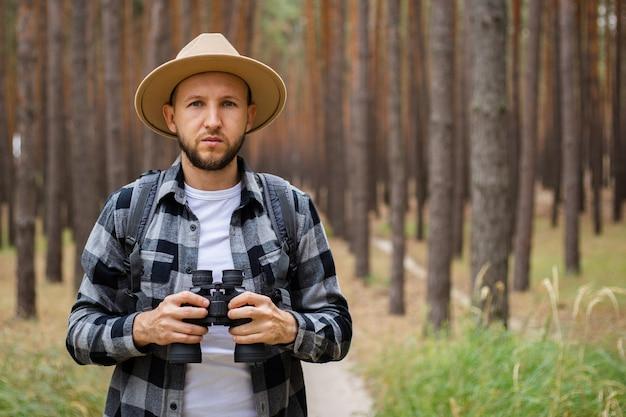 Homem com um chapéu e uma camisa xadrez segura binóculos e caminha pela floresta.