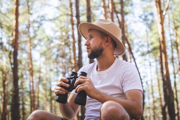 Homem com um chapéu segura binóculos durante um acampamento. caminhada nas montanhas, na floresta.