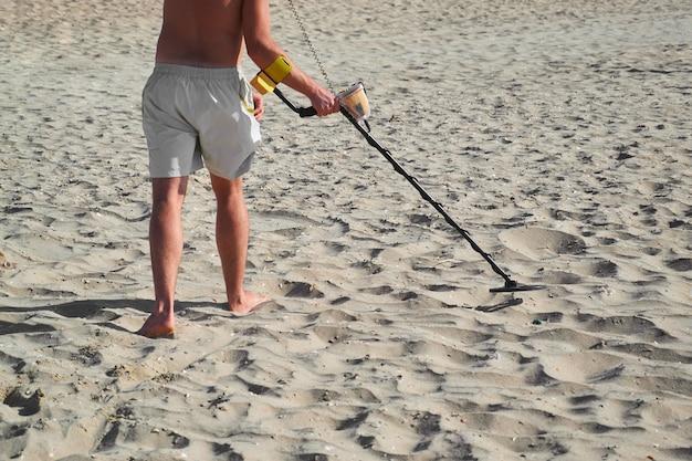 Homem com um detector de metais em uma praia de areia do mar em dia de verão