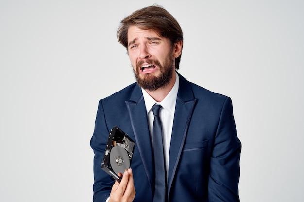 Homem com um disco rígido nas mãos, emoções, fundo claro, finanças, negócios