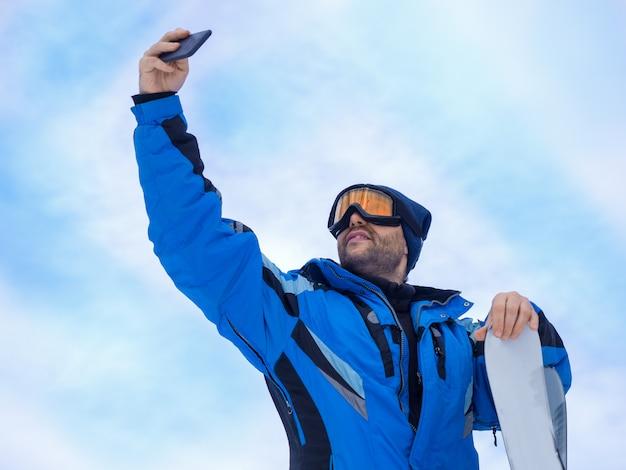 Homem com um esqui faz um selfie