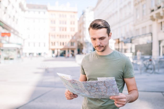 Homem com um mapa da cidade e mochila nas ruas da europa.