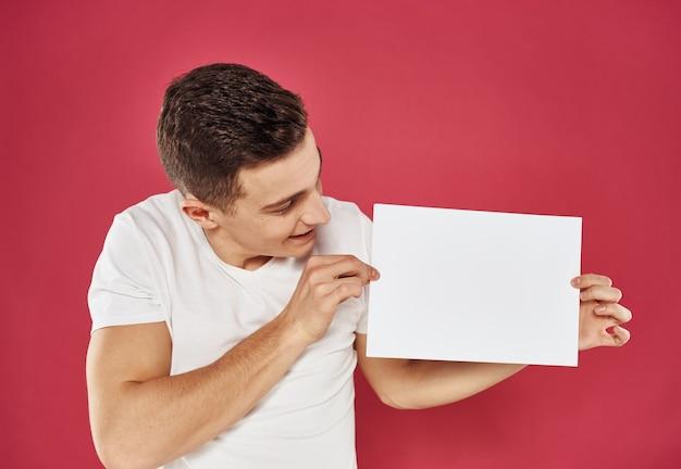 Homem com um panfleto na mão em uma maquete de publicidade de fundo vermelho.