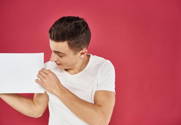Homem com um panfleto na mão em uma maquete de publicidade vermelha copy space