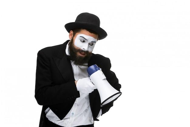 Homem com um rosto mime gritando no megafone