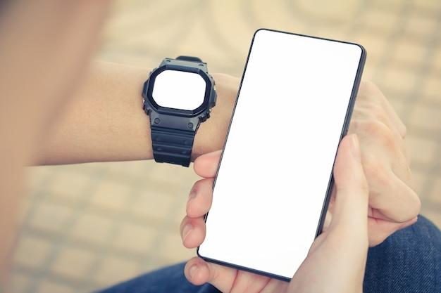 Homem com um smartwatch e smartphones