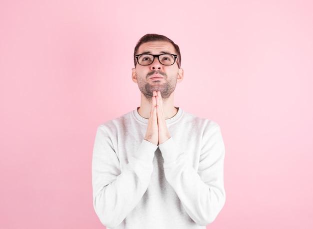 Homem com um suéter branco faz um pedido de aniversário na parede rosa.