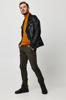Homem com um suéter laranja com as mãos nos bolsos da calça sapatos pretos jaqueta de couro estilo fashion