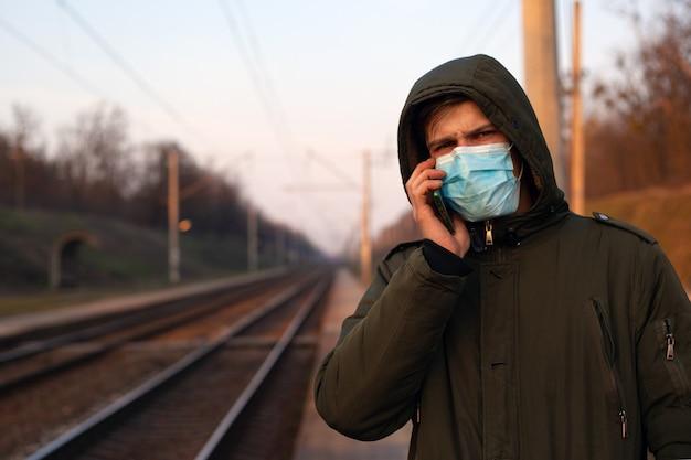 Homem com um telefone nas mãos, à espera de um trem com uma máscara médica por causa da propagação de coronavírus, surto de vírus, poluição do ar.
