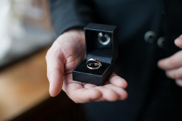 Homem com uma aliança de casamento. noivo segurando uma caixa de presente com dois anéis na palma da mão