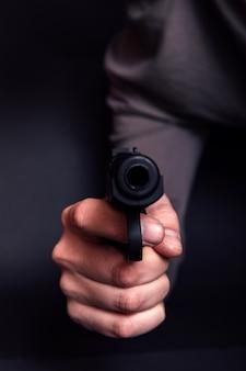 Homem com uma arma pronta para disparar, concentre-se na arma.