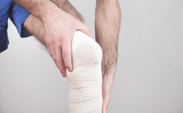 Homem com uma bandagem no joelho ferido.