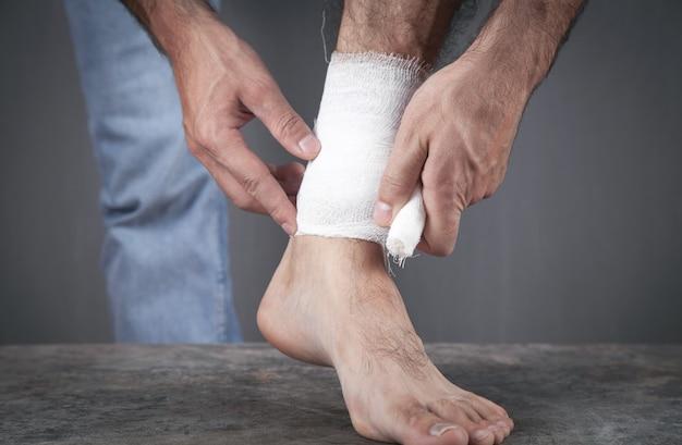 Homem com uma bandagem no pé ferido.