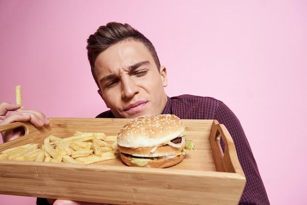 Homem com uma bandeja de junk food: hambúrguer e batatas fritas, cerveja