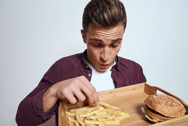 Homem com uma bandeja de junk food: hambúrguer e batatas fritas