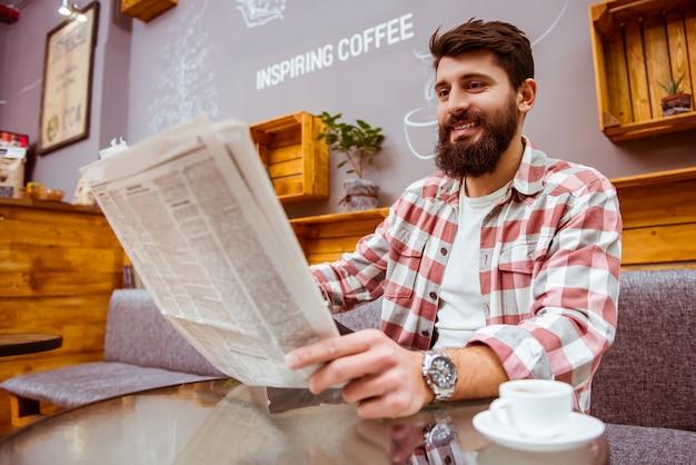 Homem com uma barba que lê um jornal e que bebe o café.