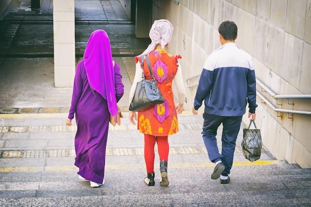 Homem com uma bolsa e duas namoradas em hijab e vestido nacional descendo as escadas para a passagem subterrânea