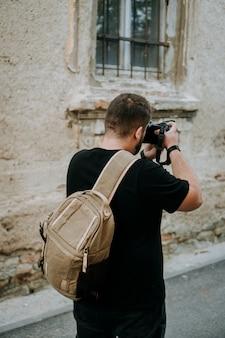 Homem com uma bolsa marrom para câmera tirando fotos em uma cidade velha