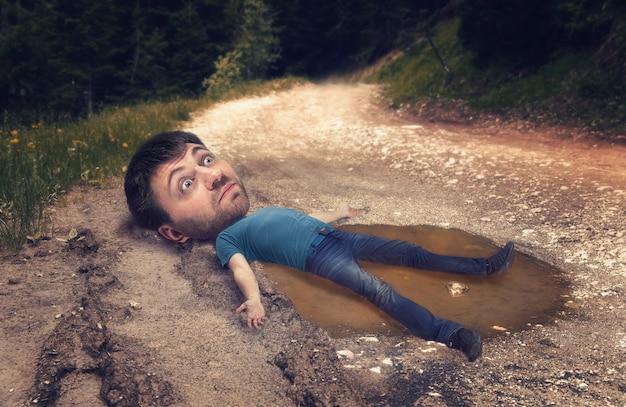 Homem com uma cabeça enorme na poça na estrada sulcada depois da chuva na floresta