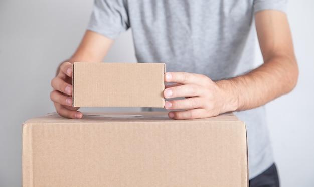 Homem com uma caixa de papelão. produtos, comércio, varejo, entrega