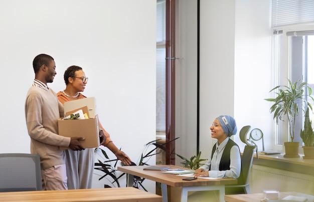 Homem com uma caixa de pertences sendo apresentado aos colegas de trabalho em seu novo emprego