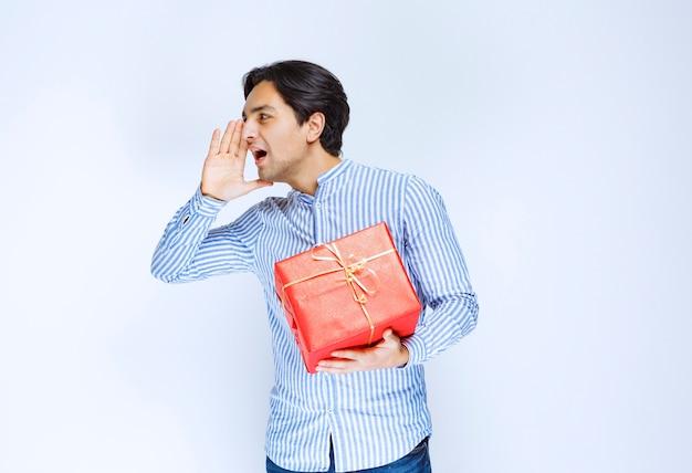 Homem com uma caixa de presente vermelha, gritando por atenção. foto de alta qualidade
