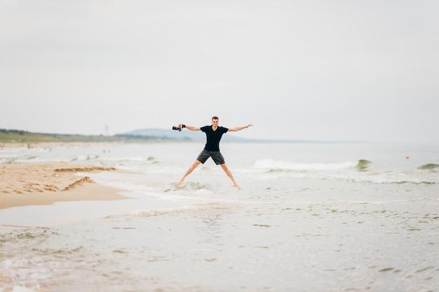 Homem com uma câmera na mão saltou em pose de uma estrela acima do mar.