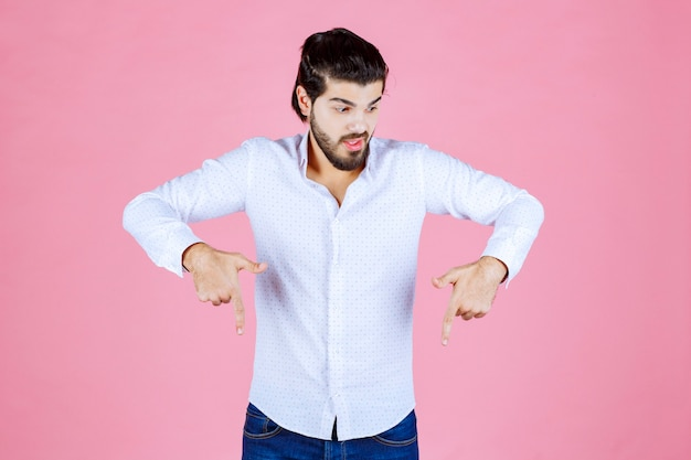 Homem com uma camisa branca apontando para baixo.