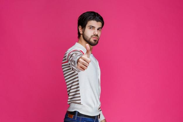 Homem com uma camisa branca, fazendo o polegar para cima o sinal.