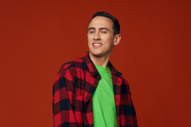 Homem com uma camisa desabotoada e uma camiseta verde sobre um modelo de sorriso de fundo vermelho