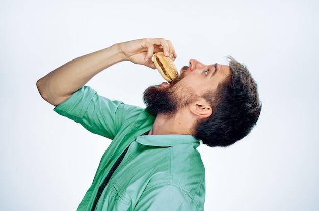 Homem com uma camisa verde comendo um hambúrguer